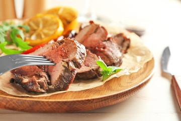 Fork and sliced tasty steak on wooden plate