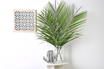 Tropical leaves in glass vase on table indoors