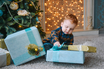 little boy sitting near boxes and opening Christmas presents