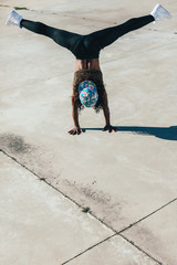 Young african american woman performing break dance in a city.