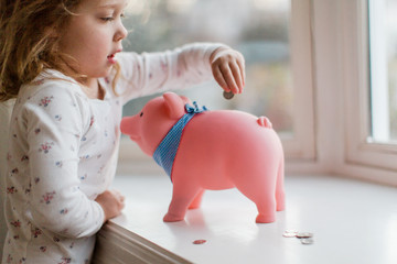 little kid putting coins into a piggy bank