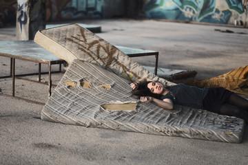 Pretty brunette girl lying on torn mattress