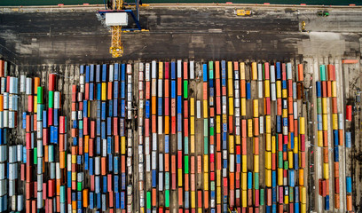 An overhead aerial view of a shipping dock quayside full of different colored shipping containers