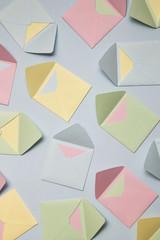 Pastel coloured envelopes on Blue Background