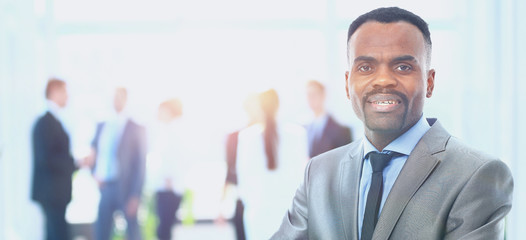 Portrait of a successful american african businessman smiling leading his team