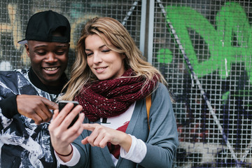 Young Multi-Ethnic Couple Looking Something at the Mobile Phone