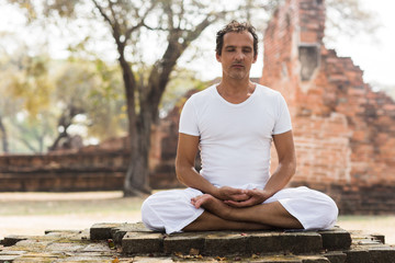 Caucasian Man Meditating in the Park