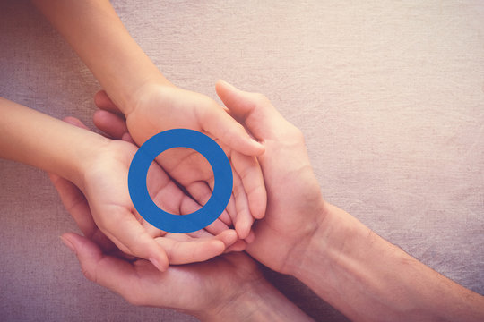 adult and child holding blue circle, copy space background, World Diabetes day