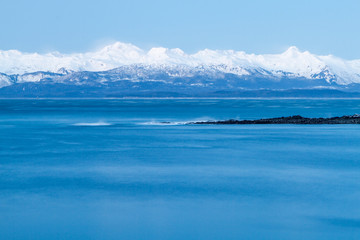 Smooth water and breaking ways of a bay with snow-covered mountains in the background