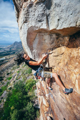 Femal rock climber on climbing and extreme rock cliff in a mountain