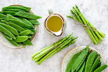 Healthy vegetarian food. Asparagus and pea near a jug of oil on grey stone background top view