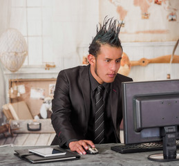 Close up of office punk worker wearing a suit with a crest, working in a computer, in a blurred background