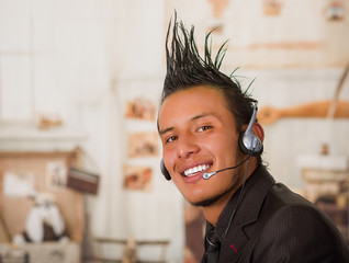 Portrait of office punk worker wearing a suit with a crest, using headphones in work, in a blurred background