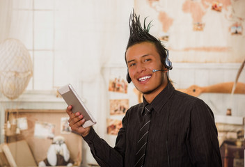 Close up of office punk man, wearing a suit with a crest, with headphones in his head and using his tablet in the office in a blurred background
