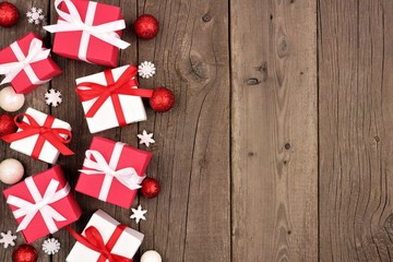 Red and white Christmas gift box side border over a rustic wood background