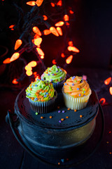 Halloween cupcakes in spooky setting with orange lights