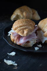 ham and swiss croissant sandwiches on dark background