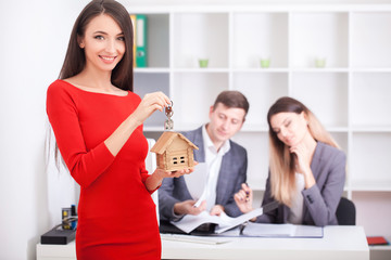 Cheerful realtor giving house key to happy property owners, young man taking keys to rented or purchased home, making deal with real estate agent, couple just signed contract and bought own flat