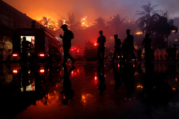 Police officers stand guard during a fire at Kandawgyi Palace hotel in Yangon, Myanmar