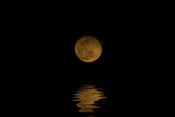 Full moon night with water reflection.