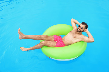 Handsome young man with inflatable ring relaxing in blue swimming pool