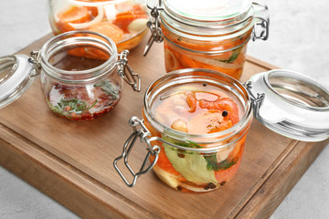 Jars with delicious marinated salmon on wooden board