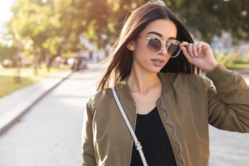 Close up fashion Outdoor lifestyle fashion portrait of young stylish beautiful woman walking on street,wearing khaki trendy outfit,biker bomber coat,black t shirt,vintage sunglasses