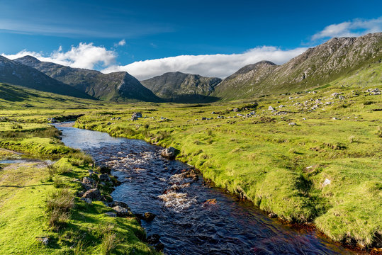 Connemara landscape in Ireland: a river flows amid the meadows in front of the majestic Twelve Bens mountains