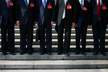 Delegates line up on the steps of the Great Hall of the People after morning sessions on the second day of the 19th National Congress of the Communist Party of China in Beijing