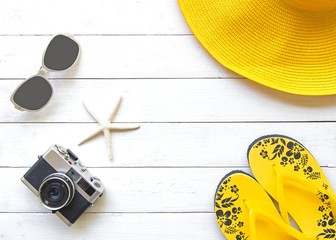 Summer Fashion woman yellow big hat and accessories in the beach. Tropical sea.Unusual top view, wood white background.  Summer Concept.