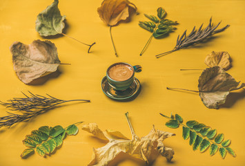 Fall coffee concept. Flat-lay of espresso cup surrounded by dried yellow and green tree leaves over mustard yellow painted wooden background, selective focus