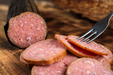 Pile of delicious smoked sausage sliced on a burnt wooden cutting board. Fork in one slice. Shallow focus on fork.
