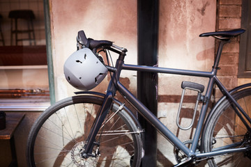 Bicycle with helmet parked against wall at city