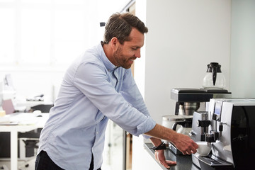 Businessman using coffee maker at kitchen counter in creative office