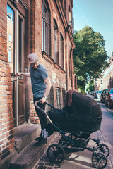Full length of man holding baby carriage while standing at entrance on building