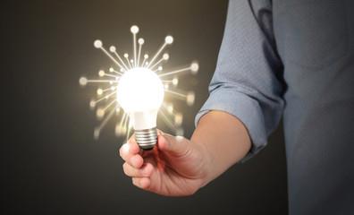 holding lightbulb in  hand