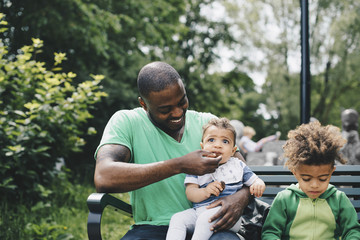 Smiling father feeding baby boy while sitting with son on bench at park