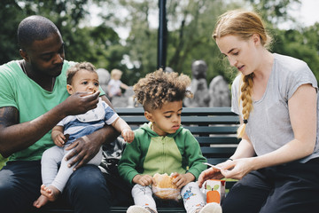 Parents having food with children while sitting on bench at park