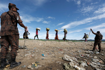 Rohingya refugees, who crossed the border from Myanmar two days before, walk after they received  permission from the Bangladeshi army to continue on to the refugee camps, in Palang Khali