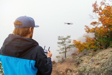 Young man handling drone, using remote control.