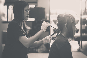 Hair coloring in a beauty salon practice close up,dyeing hair,black and white toned