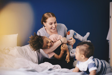 Smiling mother playing with children on bed at home