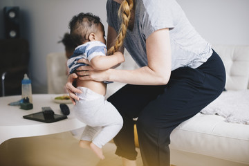 Mother carrying son while sitting on sofa at home
