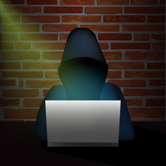 Anonymous computer hacker with hood stealing information with laptop in a dark room.