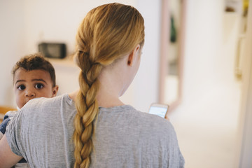 Rear view of mother with braided hair carrying son at home