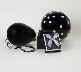 Two black balloons (one of them with white polka dots on it) and a black box with an open lid. White background.