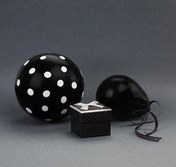 Two black balloons (one of them with white polka dots on it) and a black box with a grey satin bow on a lid. Grey background.