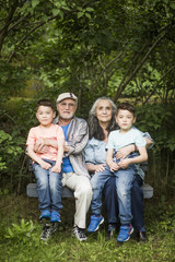 Portrait of grandparents sitting with twin grandsons on bench against plants in back yard