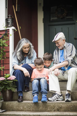 Grandparents and twin grandsons sitting at front stoop
