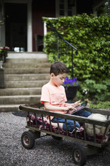 Boy using digital tablet while sitting in cart against house